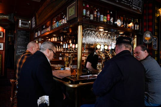 Men drink at the bar, at the Half Way Inn pub, in central Stockholm,  Monday, March 23, 2020. Bars and restaurants in Sweden are still open despite the coronavirus outbreak.