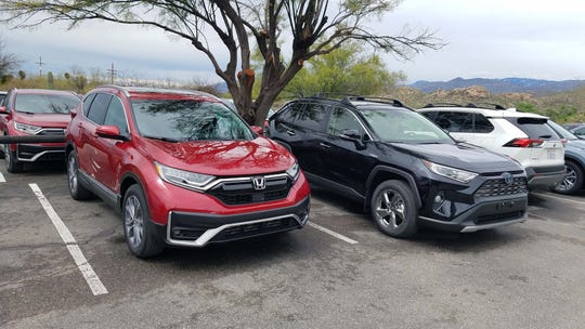 The 2020 Honda CR-V Hybrid, left, joins other class hybrids like the Toyota RAV4 Hybrid (right, in black) and Ford Escape Hybrid.