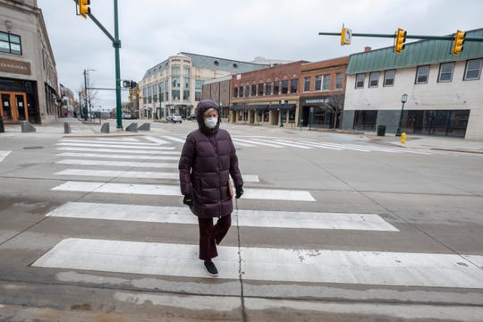 Carol Kozlow wears a mask while taking a walk on Old Woodward in a deserted downtown Birmingham, March 23, 2020.