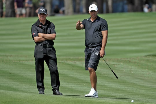 Coach Peter Cowen works with golfer Brooks Koepka, right. Cowen told a British newspaper he has the symptoms of the coronavirus but he has not been tested.