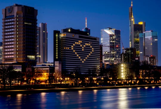 A hotel has switched on the lights in some rooms to form a heart near the buildings of the banking district in Frankfurt, Germany, Sunday, as the German government announced new public restrictions to help avoid the spread of Coronavirus.