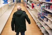 In this March 19, 2020 photo, a shopper looks for toilet paper at a Stop & Shop supermarket during hours open daily only for seniors in North Providence, R.I. Federal law enforcement is warning that scam artists are preying on older people's fears by peddling fake tests for the coronavirus to Medicare recipients.