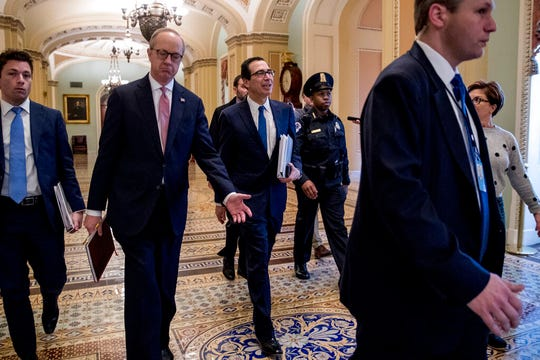 Treasury Secretary Steven Mnuchin, center, and White House Legislative Affairs Director Eric Ueland, second from left, walk to a meeting with Senate Minority Leader Sen. Chuck Schumer of N.Y. in his office on Capitol Hill, Monday, March 23, 2020, in Washington.