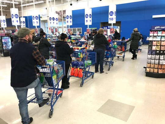 Customers wait in line at the Meijer store in Madison Heights on Monday, the day Gov. Gretchen Whitmer's stay-at-home order took effect. The order allows for grocery shopping, trips out for essential items or services and for workers deemed essential to get to work.
