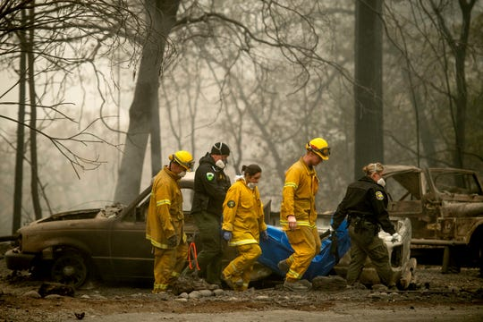 Firefighters and deputies carry the body of a Camp Fire victim Nov. 14, 2018, at the Holly Hills Mobile Estates in Paradise, Calif.