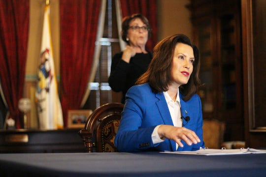 "In this photo provided by Gov. Whitmer's office, Michigan Governor Gretchen Whitmer signs the ""Stay Home, Stay Safe"" Executive Order (EO 2020-21), directing all Michigan businesses and operations to temporarily suspend in-person operations that are not necessary to sustain or protect life."