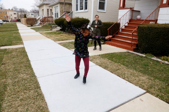 Jalen Grimes, 13, watches her 7-year-old sister, Sydney, do a cartwheel outside their home in Chicago on Sunday.