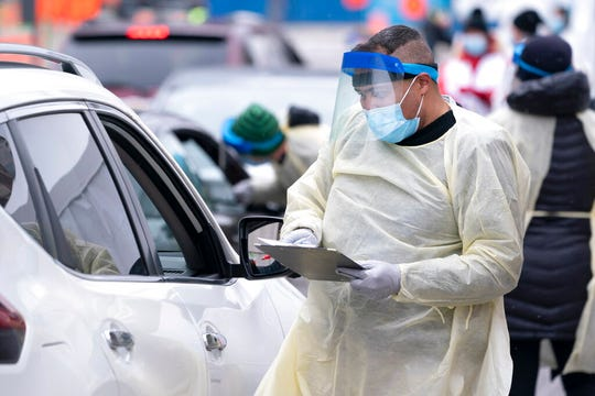 A health care worker screens people in their vehicle at a COVID-19 test clinic in Montreal on Monday, March 23, 2020.