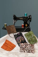 Jocelynn Brown's handmade coronavirus face masks are displayed with an antique sewing machine.