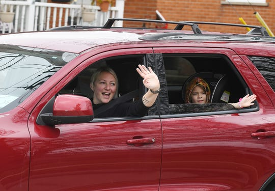 Schalm Elementary fourth grade teacher Melissa Adamczyk, along with her daughter Kinley Adamczyk, wave to students and parents as they parade around Clawson, Monday, March 23, 2020.