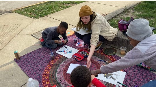 Nina Parker, 21, teaches her neighbor Jazmine Talley's children, Amari, Troy and Julius, how to paint. Parker recently lost her job in the service industry due to the shutdown ordered by Gov. Eric Holcomb to prevent the spread of COVID-19.
