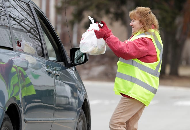 Green Bay Area Public School System food service worker Carrie Vandenheuvel hands bagged meals to a family at Eisenhower Elementary School on March 23, 2020, in Green Bay, Wis. The free pick-up meal service is available at various locations for all children while schools are closed due to the coronavirus pandemic.