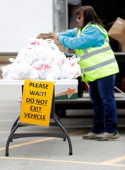 Bagged meals are organized for distribution to families as they drive through the Eisenhower Elementary School parking lot on March 23, 2020, in Green Bay, Wis. The service is available Monday through Friday for all children, but parents can pick up the food without their child present.