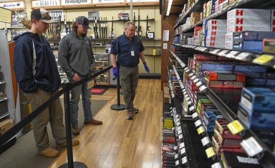 Kirkland Gillespie, left, of Pickens, and Austin Todd, middle, of Williamston listens to salesman Don Artman of Grady's Great Outdoors in Anderson explain what supplies of ammo they have for sale Monday, March 22, 2020.
