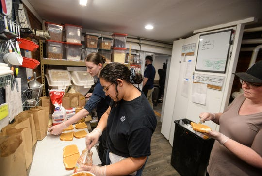 Jordan Shope, left, Salysia Farmer, center, make peanut butter and jelly sandwiches at the Double Barrel Coffee House Cafe on Monday, March 16, 2020.  The cafe was offering brown bag lunches to any community members that need them.