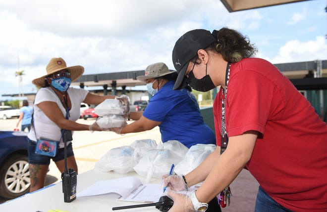 Wettengel Elementary School employee Tricia Rosario, right, keeps track of the drive-up meal count during Guam Department of Education's Grab-N-Go School Meal Program at Wettengel Elementary School in Dededo, in this March 23 file photo.