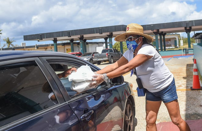 """Nette Cruz, a Wettengel Elementary School employee, distributes free lunches to families during Guam Department of Education's """"Grab-N-Go"""" School Meal Program at her school's campus in Dededo, March 23, 2020."""