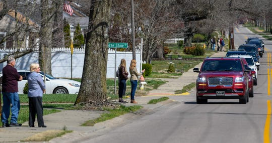 Mourners stand along South Main Street in Henderson during the funeral procession for longtime Henderson educator Bobby Liles. Under current guidelines, funerals are limited to 10 people total -- including family members.
