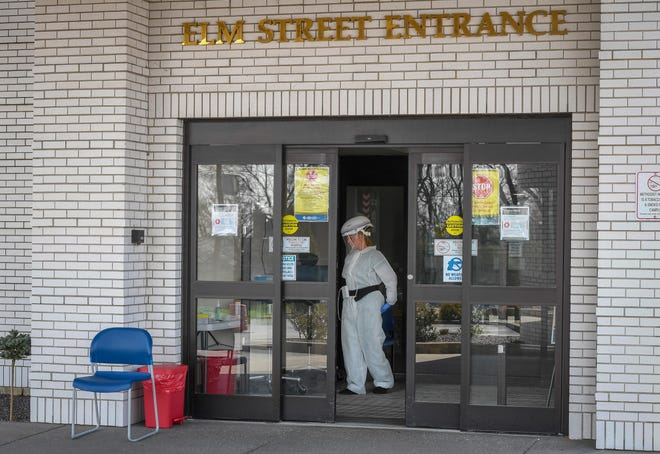 An employee wearing protective equipment at Methodist Hospital's main entrance stands ready Monday to test people that are approved for drive-up testing through a screening process.