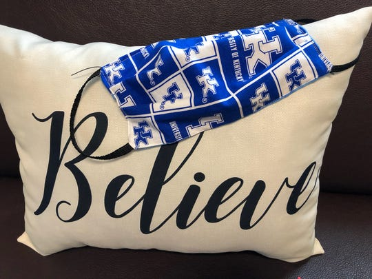 "One of the masks made by the Job Corps staff members lays across this ""Believe"" pillow."