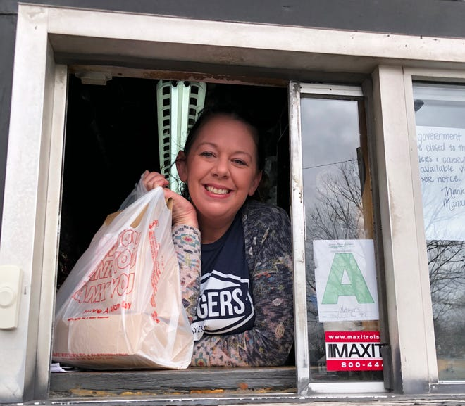 Katie Beth Pritchett, general manager of Metzger's Tavern, prepares to hand over a carryout meal from its drive-thru window. The venerable institution last week began offering online ordering to facilitate carryout orders since dining-in has been suspended at restaurants and bars by the order of Kentucky Gov. Andy Beshear.