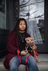 K.C. Campbell, a line cook at Mayfair Taproom, poses for a picture with Staffordshire terrier Pikey outside of Mayfair Taproom.