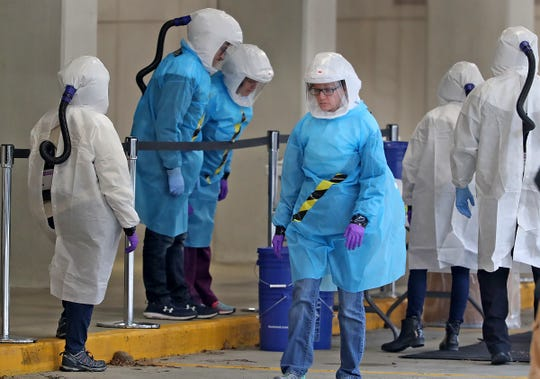 Workers in hazmat suits prepare for drive-through COVID-19 testing at Lilly, Monday, March 23, 2020.  Testing is for Indianapolis health care workers.