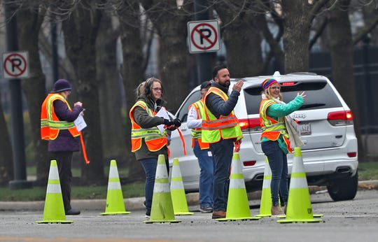 Workers guide drivers in a check-in line for drive-through COVID-19 testing at Lilly, Monday, March 23, 2020. Drivers are asked to keep their windows rolled up, stay in their cars and show appointment confirmation for the test. Testing is for Indianapolis health care workers.