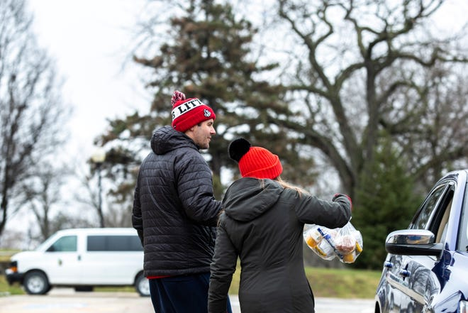 Iowa City High Principal John Bacon, left, and Assistant Principal Natalee Swan deliver bags of food to families at a drive up pickup location while schools are closed, Monday, March 23, 2020, at City High School in Iowa City, Iowa.