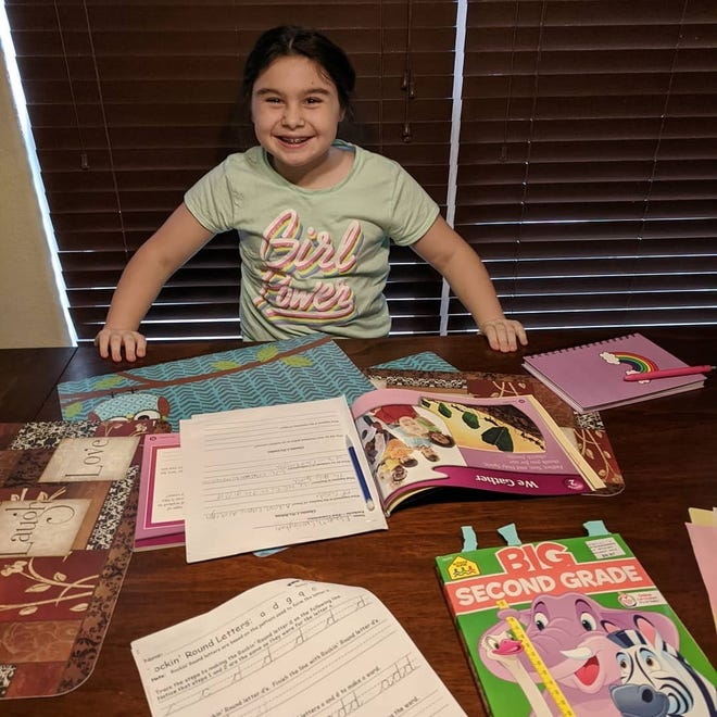 Elizabeth Cunningham, 8, is learning from home with help from her parents and workbooks while schools are closed.