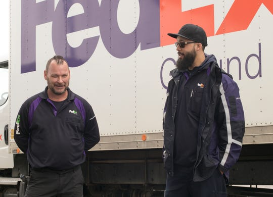 FedEx drivers Kevin Goulette, left, and Adam Hampton talk Monday, March 23, 2020 about the challenges of being on the road and trying to make deliveries to businesses, many of which are closed, in the wake of the COVID-19 pandemic.