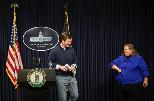 Sign interpreter Virginia Moore gives an elbow wave -- now a common way to say hello or thank people instead of shaking hands -- to a smiling Gov. Andy Beshear after a March 23, 2020 briefing to the commonwealth of Kentucky about the coronavirus outbreak that has swept the state. March 23, 2020