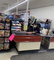 Staff at a Darrell's Market & Hardware wear face masks while they work on Monday, March 23, 2020.