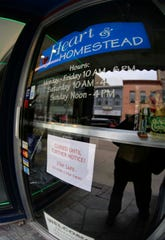 A sign on the door of Hearth and Homestead as seen, Monday, March 23, 2020, in Manitowoc, Wis.