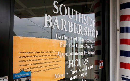 A sign on the Southside Barbershop tells of the temporary closure, Monday, March 23, 2020, in Manitowoc, Wis.
