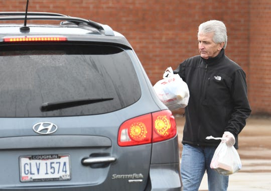 Lexington superintendent Mike Zieglhofer passes out free lunches  Monday afternoon at Lexington High School.