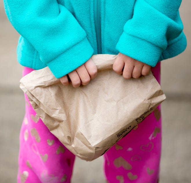 Kindergarten student Mackenzie Villanueva, 6, holds on to her bagged lunch on Monday, March 23, 2020, at Ed Rice Community Center in Memphis.