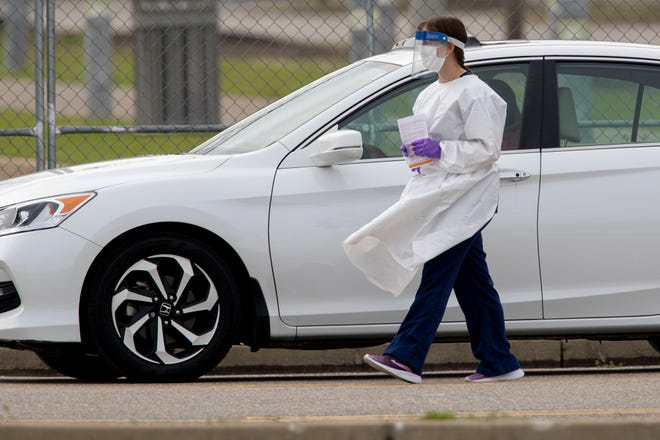A COVID-19 test site worker walks alongside a motorist Monday, March 23, 2020, at the Memphis fairgrounds.