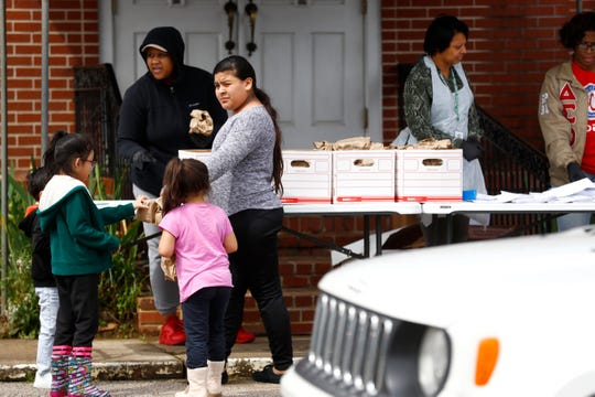 Workers hand out Shelby County Schools K-12 learning packets and meals for children from Abundant Grace Fellowship Church on Shelby Drive Monday, March 23, 2020.
