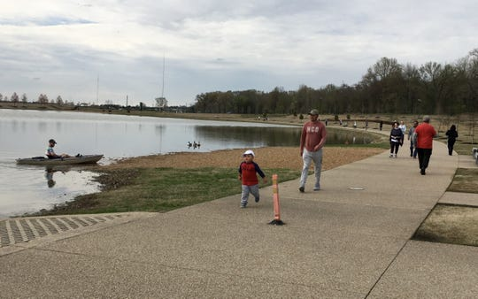 Jacob Allen (left) lands his kayak in Shelby Farms as parkgoers enjoy spring weather on March 23, 2020.