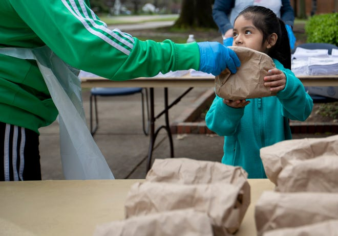 Cassandra R. Tucker (left) hands a bagged lunch to Mackenzie Villanueva, 6, on Monday, March 23, 2020, at Ed Rice Community Center in Memphis.