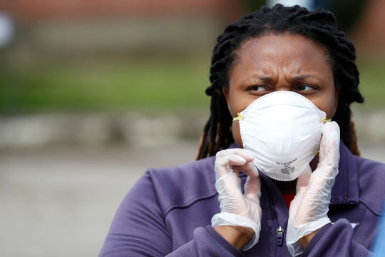 Mary Olds adjusts her protective face mask on a break in handing out Shelby County Schools K-12 learning packets and meals for children from Abundant Grace Fellowship Church on Shelby Drive Monday, March 23, 2020. The district school system has set up dozens of access points across the city in hopes of reaching children in need of nourishment and coursework supplies as the schools have shut down indefinitely over concerns of the spread of coronavirus.