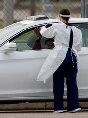A test site worker hands a piece of paper through the car window Monday, March 23, 2020, at the COVID-19 testing site at the Memphis fairgrounds.