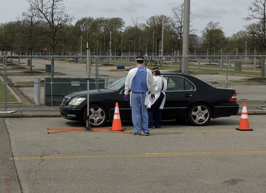 Workers in gowns, gloves and face shields talk with a driver during an initial screening at the new Memphis drive-thru coronavirus testing center on Monday, March 23, 2020. This driver was not allowed to proceed further into the testing center and pulled over to the side of the road, apparently to make calls.