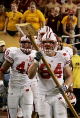 Dejected Minnesota fans, background, watch as Wisconsin's Jason Pociask carries the coveted Paul Bunyan's Axe as teammate Elliot Goode, left and other happy Badgers players celebrate Wisconsin's 38-34 come-from-behind victory over Minnesota.