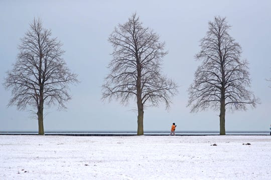A jogger runs along the Lake Michigan lakefront near Veterans Park in Milwaukee on Monday.