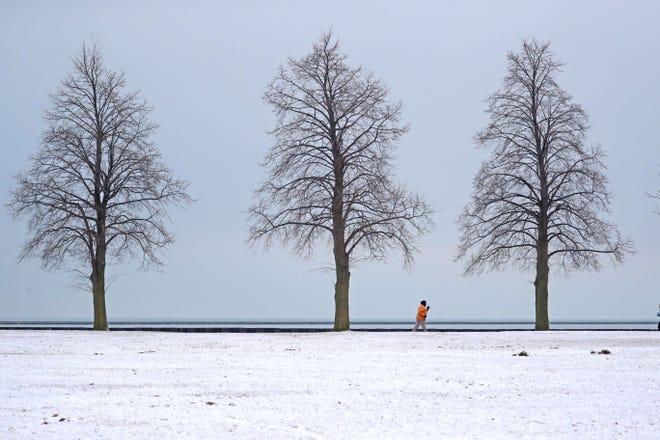A jogger runs along the Lake Michigan lakefront near Veterans Park in Milwaukee on Monday.