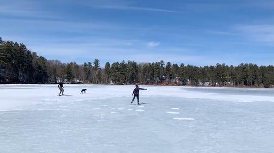 A skier and an ice skater race on Lower Kaubashine Lake near Black's Cliff Resort in Hazelhurst on Saturday.