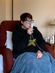 Sarah Acker, 59, does a breathing treatment at her home in Glendale.