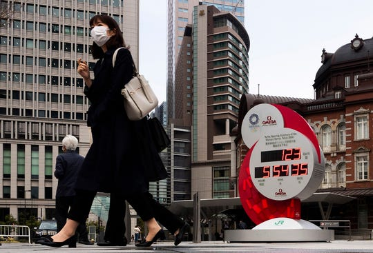 A countdown clock for the Tokyo 2020 Olympics sits outside Tokyo Station on Monday in Tokyo. The International Olympic Committee has decided to postpone the Games, a committee member said Monday. Read more in Sports, 1B.